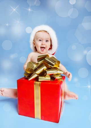 Expressive baby sitting with Christmas present photo