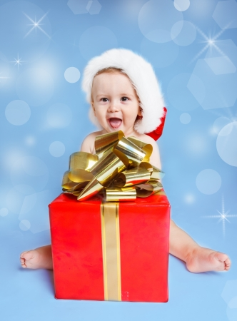 Funny laughing little boy in Santa hat sitting beside red Christmas present photo