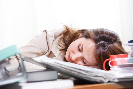 Businesswoman sleeping among papers and coffee cups photo