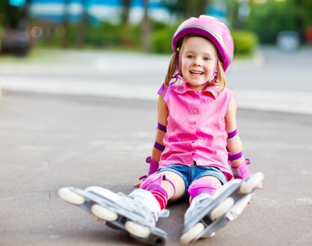 elbow pad: Cheerful roller skater in protective equipment sitting on the ground