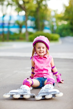 Little roller skater with skets and pink protective equipment on photo
