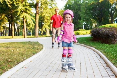 beginner: Preschool beginner in roller skates in front, and dad behind