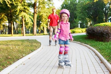 niño en patines: Principiante Preescolar en patines de ruedas en el frente, y detrás de papá