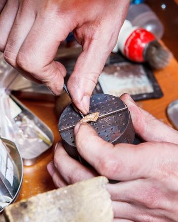 precise: Hands of a jeweler creating golden earring