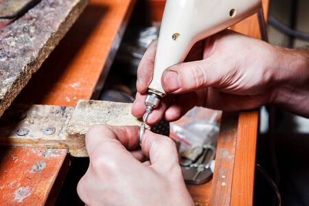 engraver: Jewelers hands engraving on the ring Stock Photo