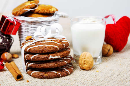 Cookies, nuts, milk and red decoration photo
