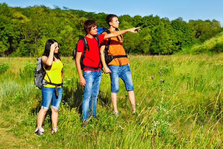 Teenage backpacker showing way to his friends Stock Photo - 16609488