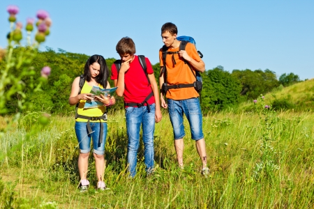 Puzzled hiking teenagers looking into map photo