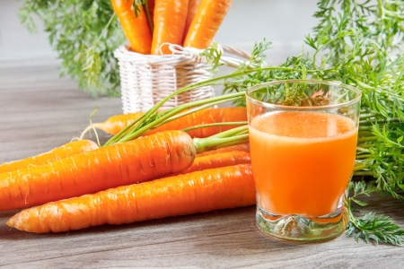 Carrot juice in glass and vegetables beside
