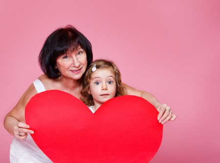 Grandmother and little girl holding large red paper heart photo