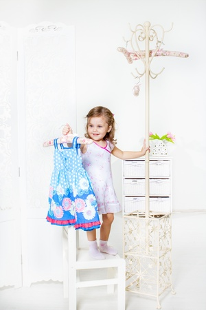 Laughing little girl looking at her dress on the coat hanger photo