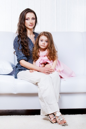 Mother and daughter on the white sofa photo