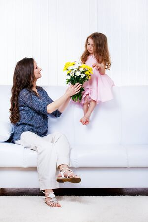 Mother with  flowers bouquet and little daughter sitting on sofa photo