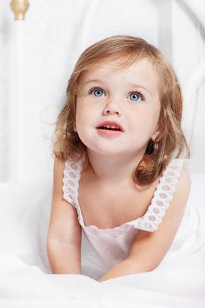 Portrait d'une petite fille couchée dans son lit