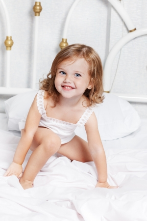 Pretty smiling girl sits in bed photo