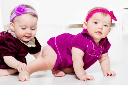 crawl: Two cute female toddlers playing