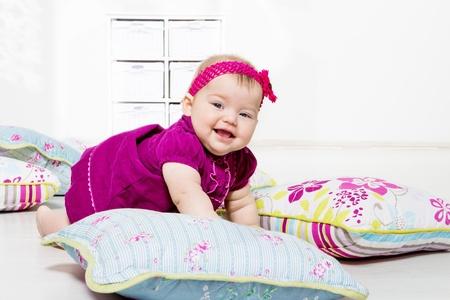 bebe gateando: Riendo niña en vestido arrastrándose entre almohadas