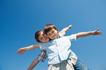 Two kids with their arms open wide over blue sky Stockfoto