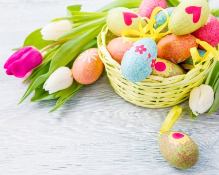 Easter eggs lying in basket and flowers beside  photo