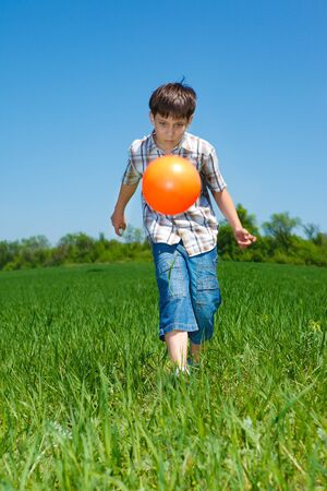 Boy playing with a ball in the countryside photo