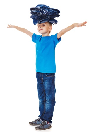 Boy in blue clothing holding denim wear pile on head Stock Photo - 17798585