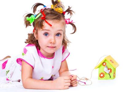 maison oiseau: Dr�le fille d'�ge pr�scolaire de jouer avec la d�coration maison d'oiseau