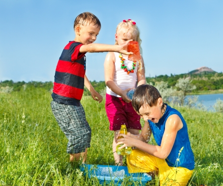 Kids splashing water in the meadow photo