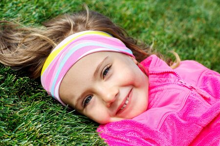 Portrait of a preschool girl on green grass photo