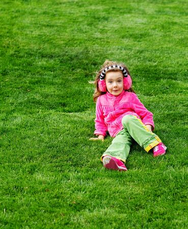 Cute cheerful preschool girl sitting on the hill photo