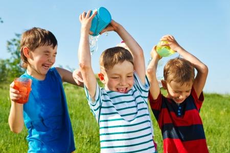 niños jugando en el parque: Felices los niños con containes plástico salpicaduras de agua sobre la cabeza de un anothers ' Foto de archivo