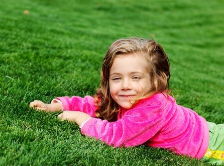 Portrait of a cute cheerful preschool girl in park photo