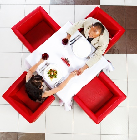 Top view on middle aged man and woman holding hands in a restaurant Standard-Bild