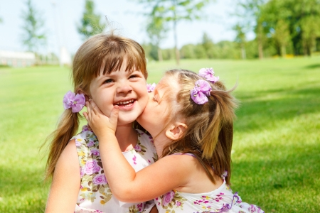 Cute girl kissing her laughing sister photo