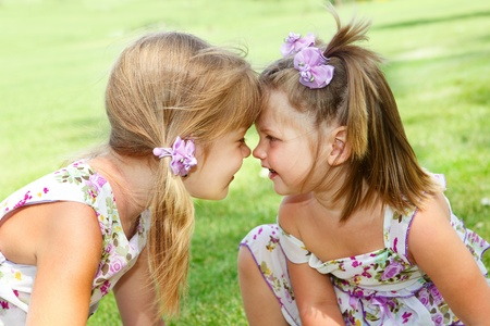 Two little sisters looking at each other photo