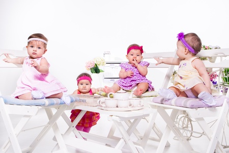 Adorable babies group having tea party photo