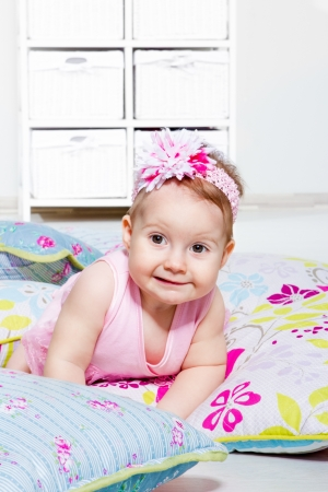 Lovely baby girl lying on the  pillows with floral pattern photo