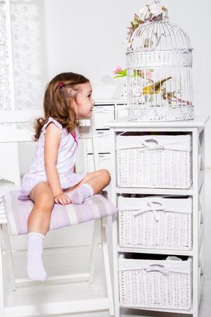 petite fille avec robe: Etonné fille regardant l'oiseau en cage