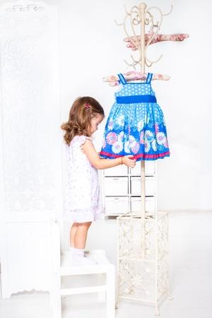 kids dress: Preschool girl standing on the chair beside coat hanger with a little dress Stock Photo
