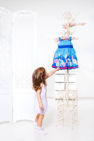 willing: Little girl willing to get dress from the coat hanger