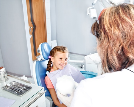 regular people: Little smiling patient looking at dentist