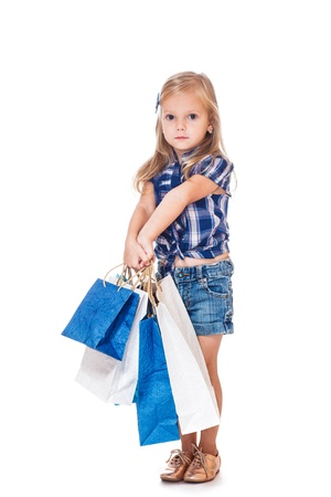 blue jeans kids: Beautiful preschool girl holding blue and white shopping bags