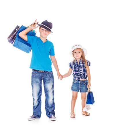 kids wear: Fashionable children holding hands and shopping bags Stock Photo