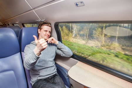 Happy passenger in train showing thumb up