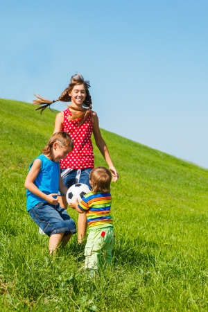 school sports: Three laughing kids playing with a ball on green grass