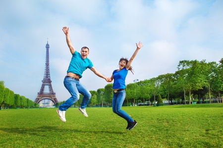 la tour eiffel: Excited young couple jumping in front of the Eiffel Tower in Paris