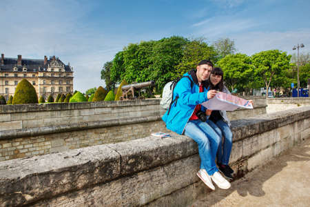 Young traveling couple sitting with a map in front of the Invalides complex in Paris photo