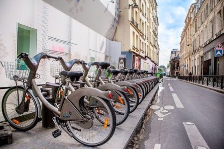 segregated: PARIS- MAY17: Rental bicycles on May 17, 2013  in Paris, France. Row of the gray city bikes for rent and a segregated cycling path painted with marking Editorial