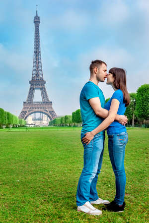 kiss couple: Kissing young couple in front of the Eiffel Tower in Paris Stock Photo