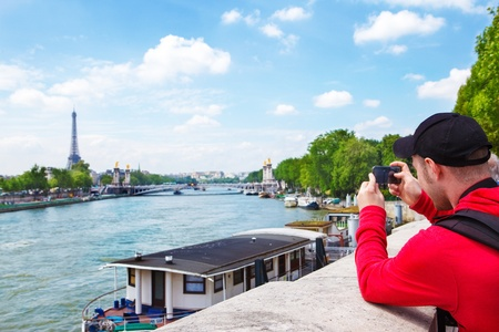 Tourist in Paris making photos of Seine river and the Eiffel tower photo