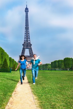 la tour eiffel: Happy young couple running in front of the Eiffel Tower in Paris